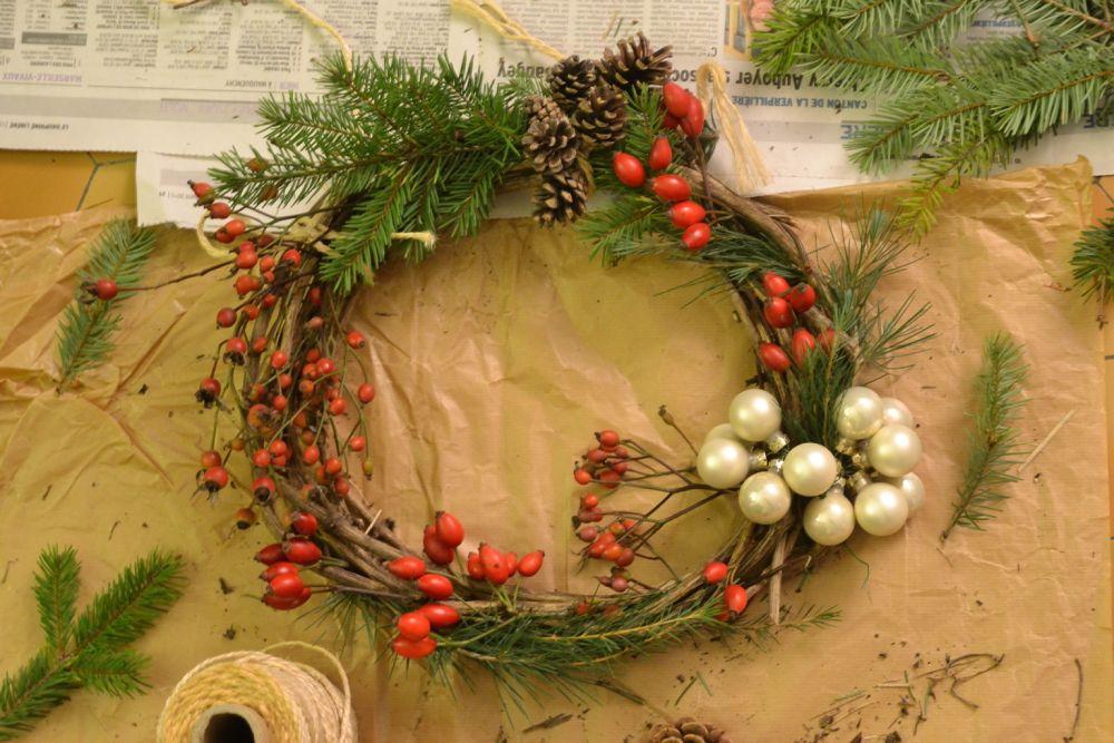la couronne de noël : on ajoute les décors, baies de rosier, branches sapin, pommes de pin